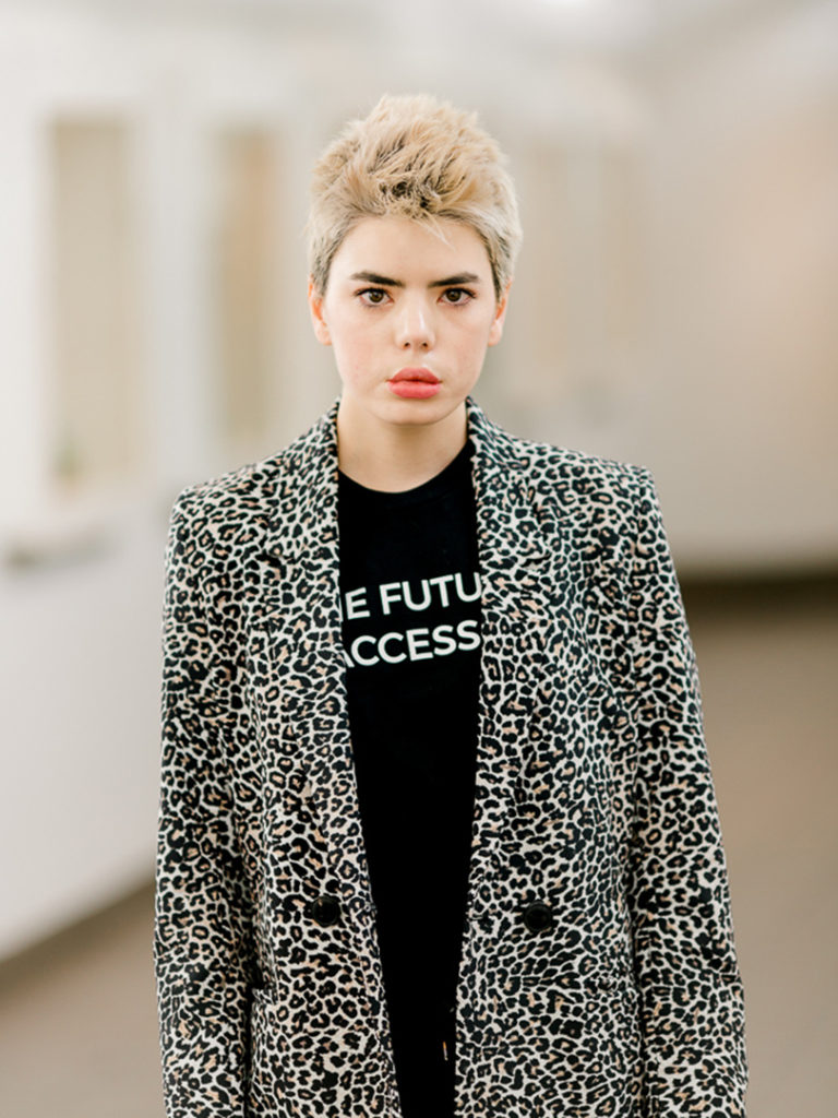 A photograph of Kristina McMullin taken by Michelle Peek of Bodies in Translation. She looks into the camera with a neutral, albeit a bit tired, look on her face. She has short dyed blond hair and dark brown eyebrows and eyes which contrast against her fair skin. She wears a black and white leopard blazer over a black shirt with white all caps lettering. Some of the lettering is obstructed, but the slogan reads 'The Future Is Accessible'. Kristina stands apart from the out of focus background.