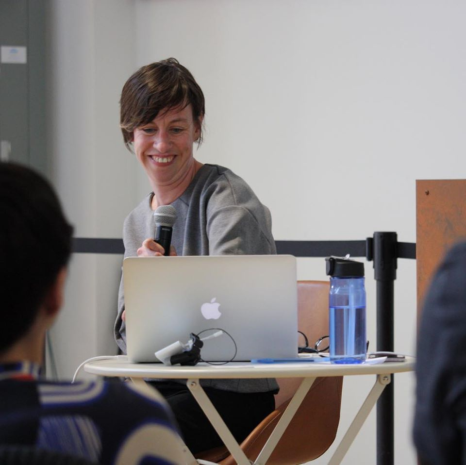 Photo credit: Kayla Besse Image description: Eliza is a white, cis-gendered, noticeably disabled woman. She has brown short hair and in this photo, she is wearing a grey top, sitting behind a laptop, holding a microphone, and she is smiling.