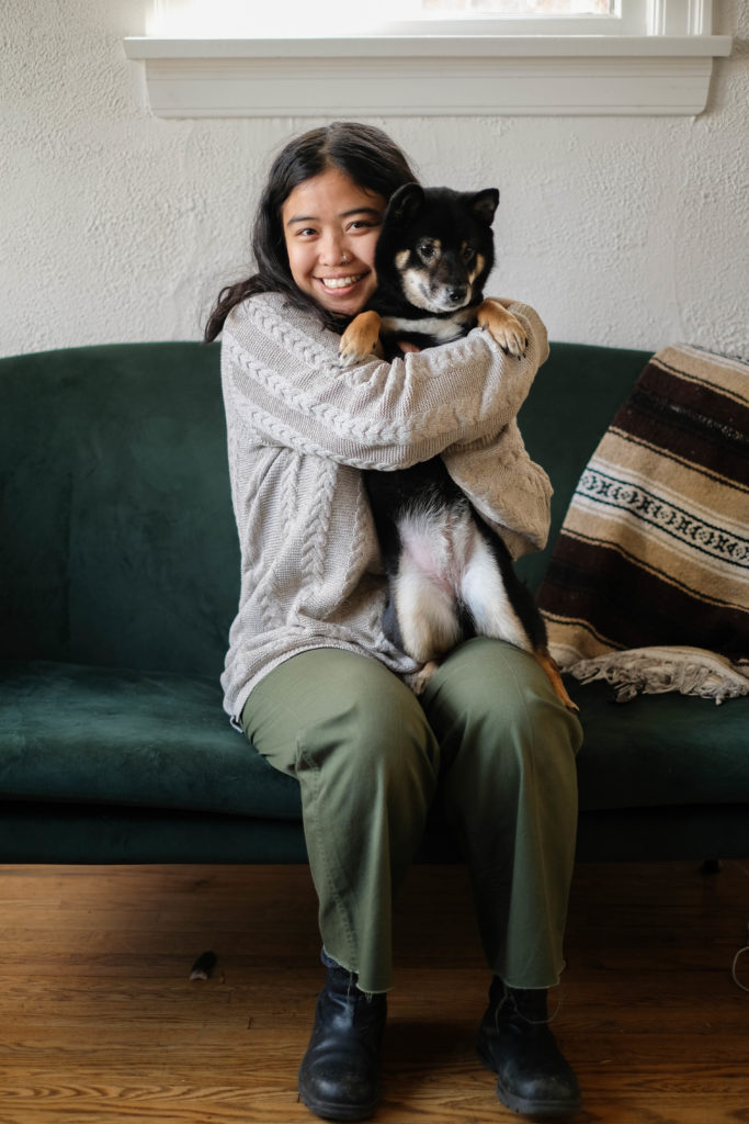Image Description: A photograph of Alexis hugging their black and tan shiba inu, Satomi, sitting on an emerald green velvet couch. A striped woven blanket is draped along the back of the couch. The image captures Alexis' full sitting body. Satomi is on her hind legs, balancing on one of Alexis' legs, and Satomi's underbelly is showing. Alexis is smiling at the camera with their face squished up against Satomi's face. Satomi's tan paws resting on Alexis' wrapped arms. Alexis has wavy, mid-length brown hair that collects messily along her shrugged shoulders. Their skin is an almond tone. Alexis is wearing a knitted light beige sweater, green pants, and black boots.