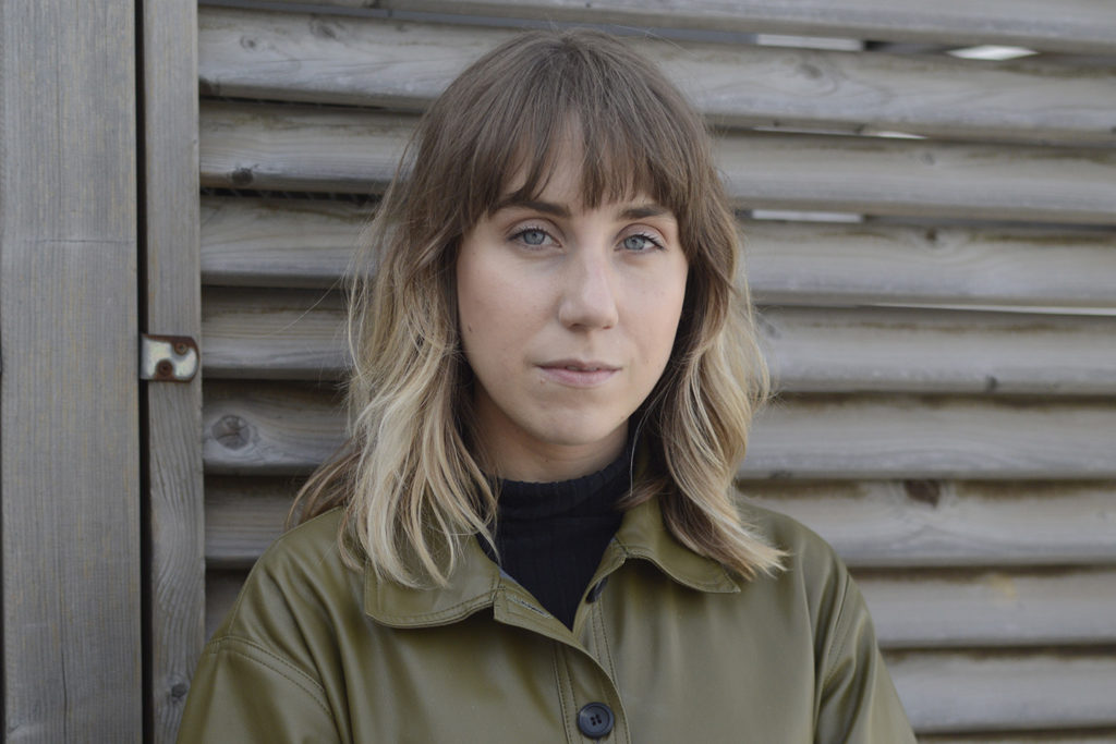 A Photo of Phillipa. She is a white woman with light brunette hair and blue eyes. She wears a green buttoned jacket and a black turtle neck top. She looks at the camera with a serious gaze while in front of a wood panelled wall.